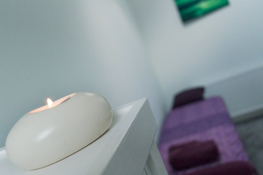 Lit candle with purple massage table in the background
