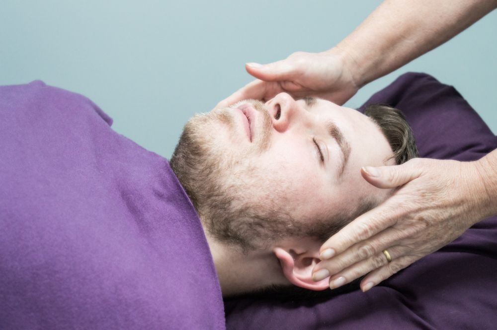 Man receiving reiki - hands help either side of head