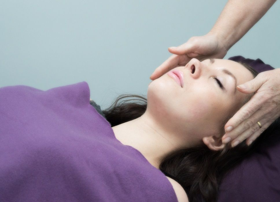 Woman receiving reiki - hands help either side of head